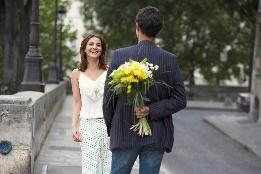 Caballero llevando flores a una chica en una cita romántica